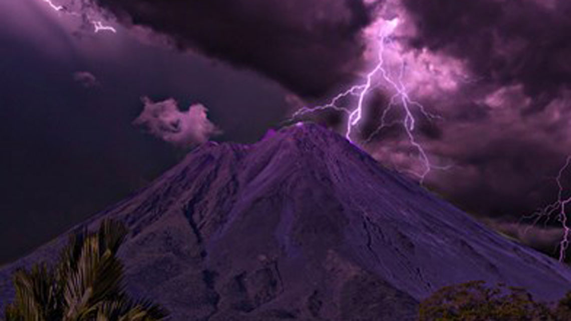 Arenal volcano in a thunderstorm at night