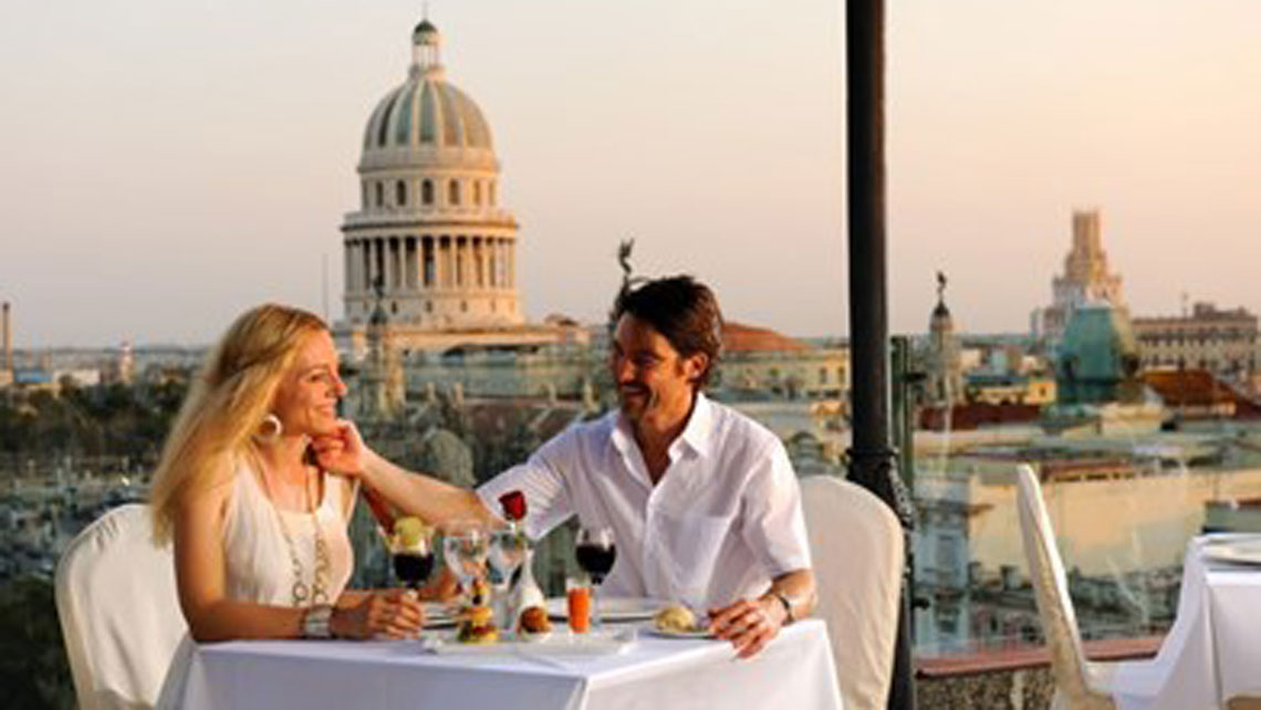 A couple dining on a rooftop with panoramic views of Havana