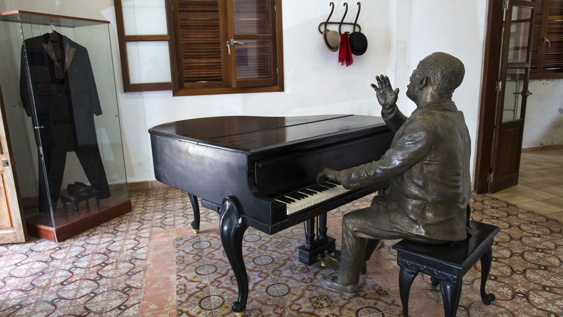 Bronze statue of Bola de Nieve playing the piano in his old house in Regla