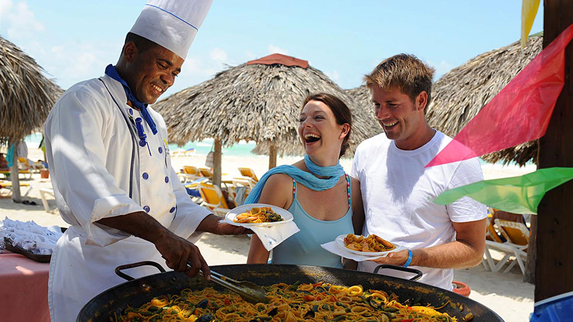 Tourists and a member of a hotel staff laughing