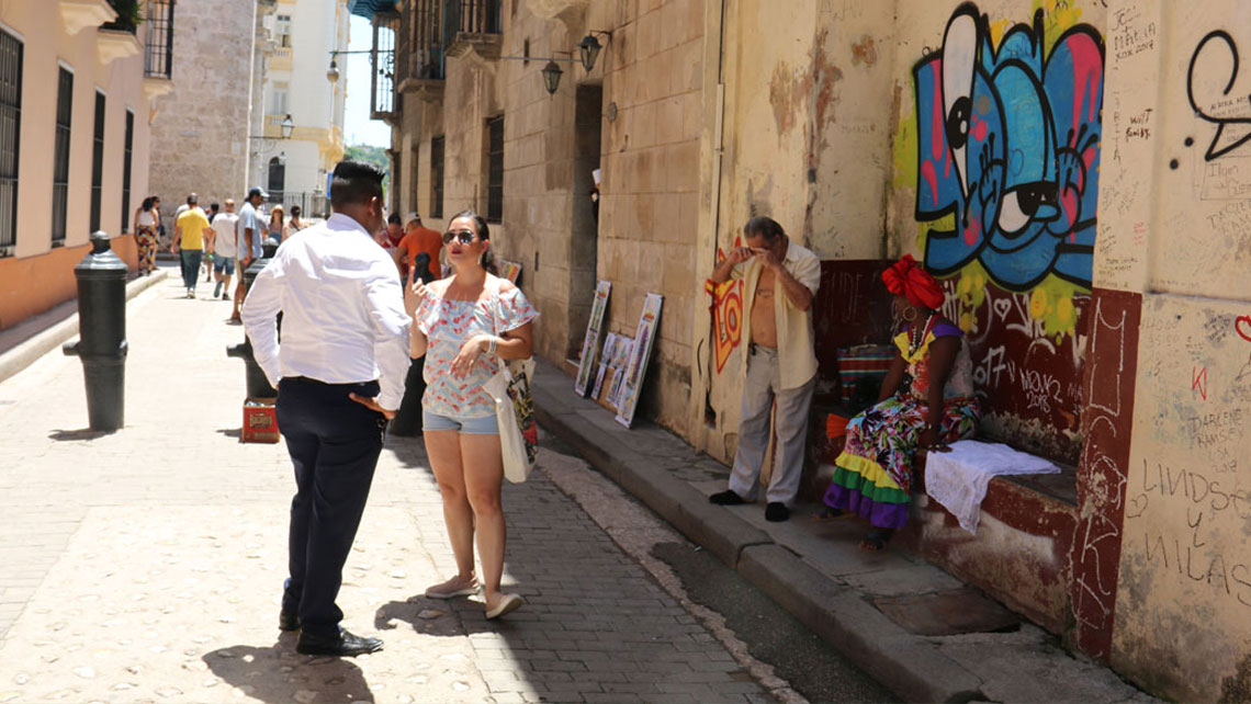 Two person having a conversation on a street in Havana