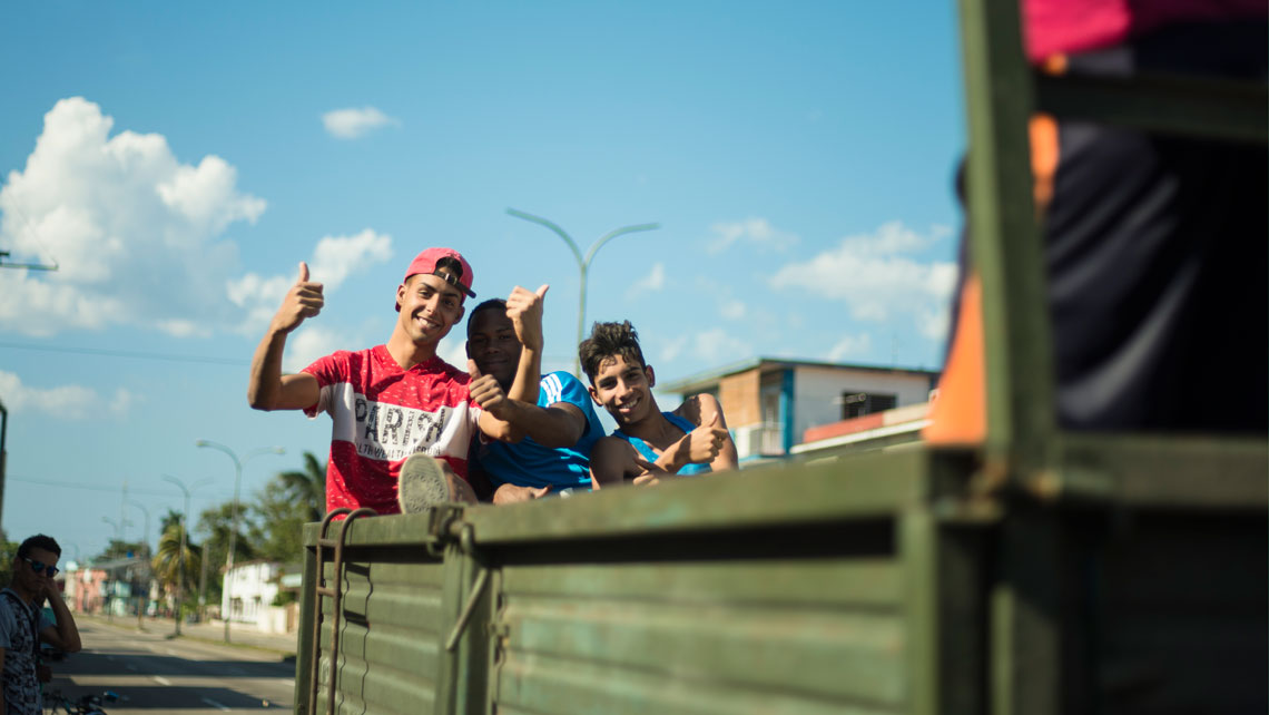 Young men saying hello from the back of a truck