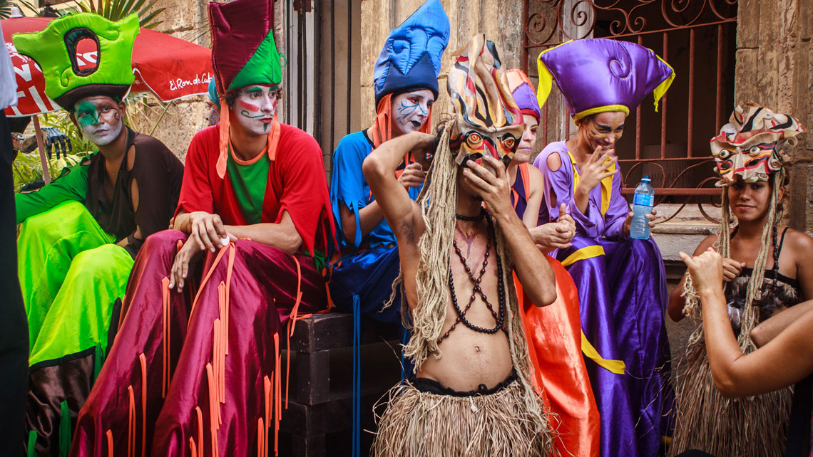 A group of street performers dressed in colorful costumes hanging out in a street of Old Havana