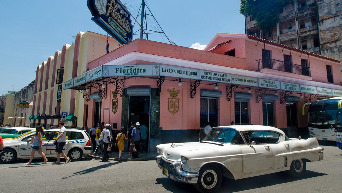 Vintage American car taxi passing in front of El Floridita Bar(a Hemingway hangout)