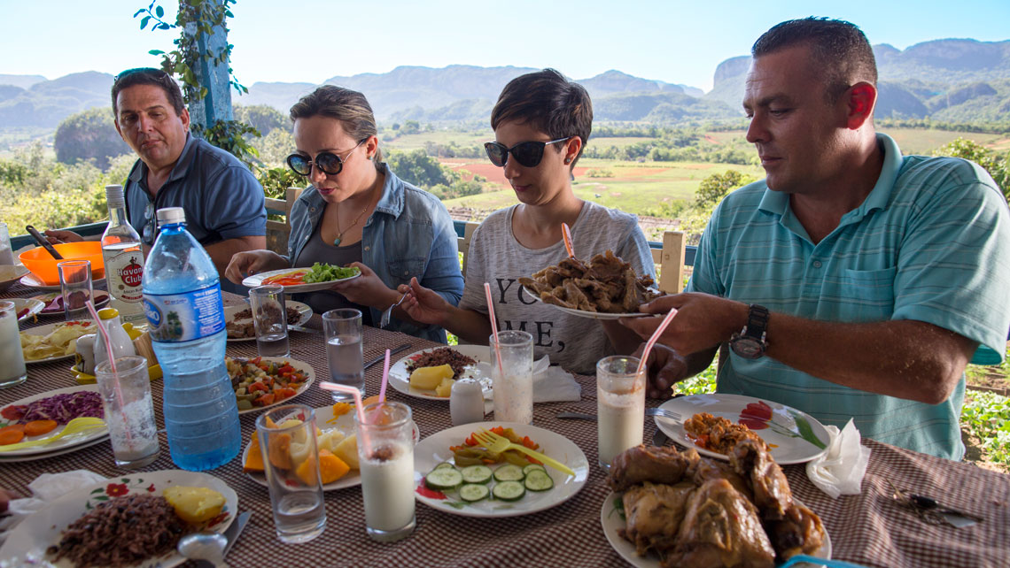 People having traditional Cuban food in an agro-ecological restaurant in Viñales