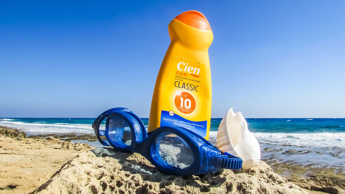 A bottle of sun cream and a pair of swimming googles on a sandy beach