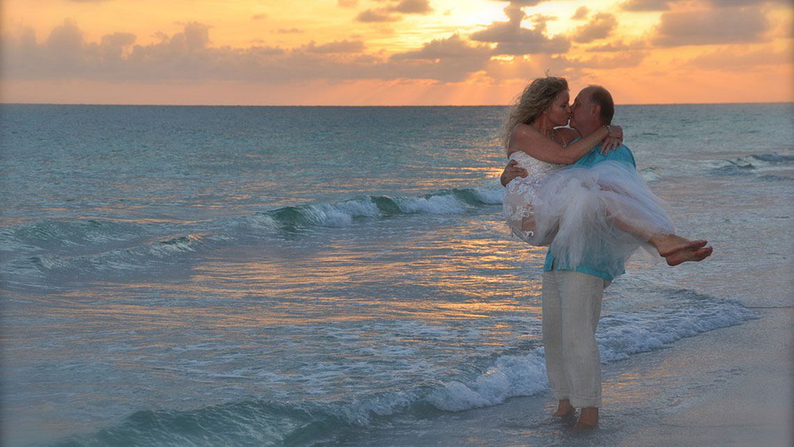 A couple kissing in a beach at sunset