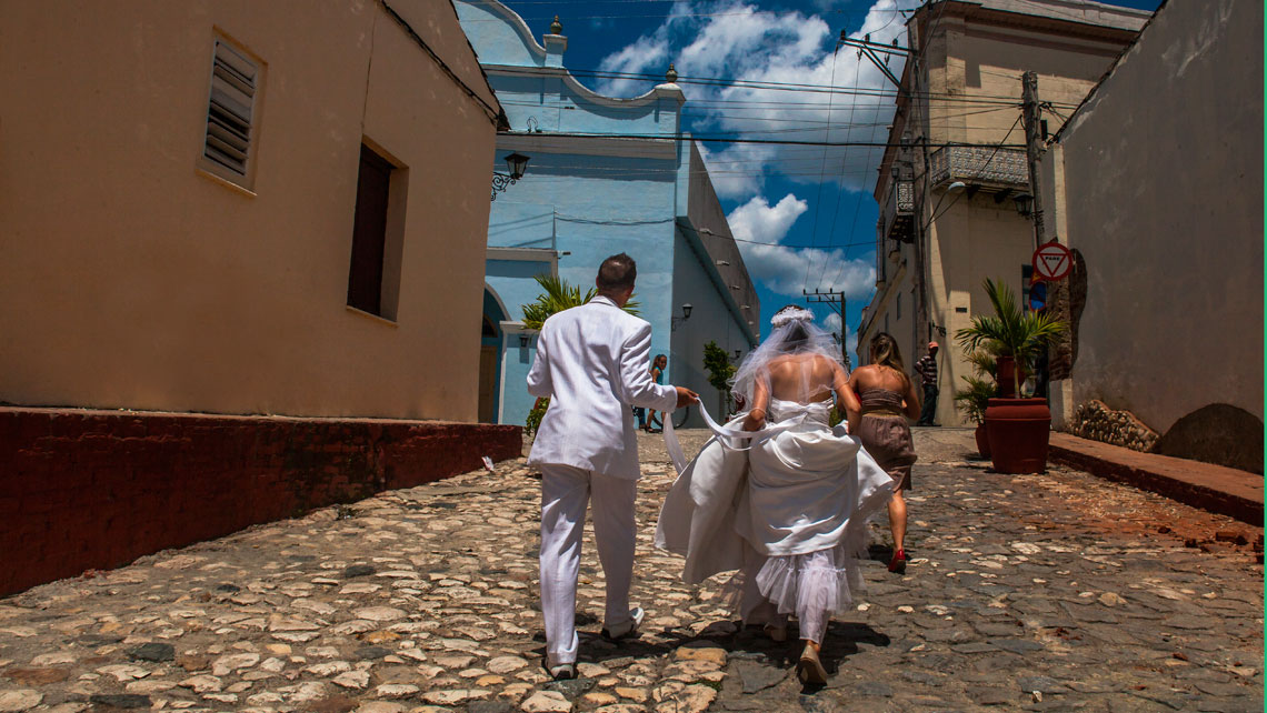 Newlyweds walking on a cobbled street in Sancti Spiritus
