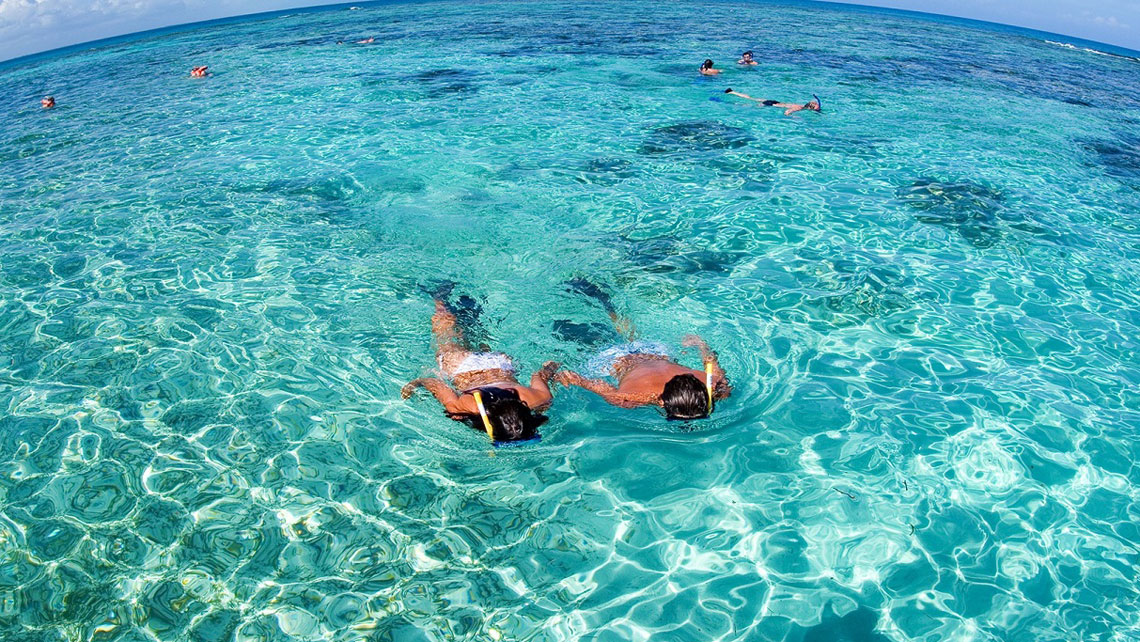 A couple snorkelling in cristal clear waters