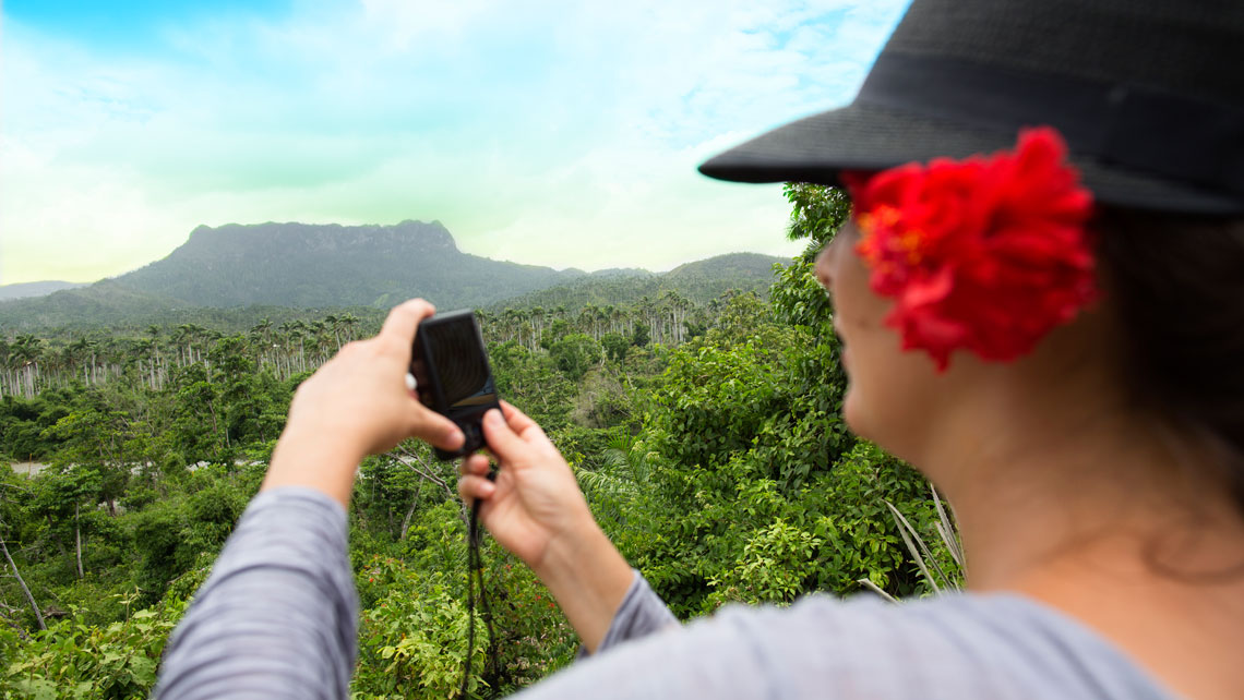 A female traveller taking a picture of El Yunque mountain in Baracoa