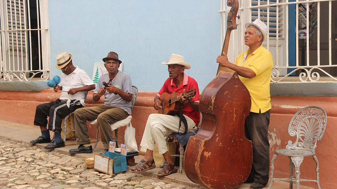 Local band performing on the sidewalk of a cobbled street in Trinidad