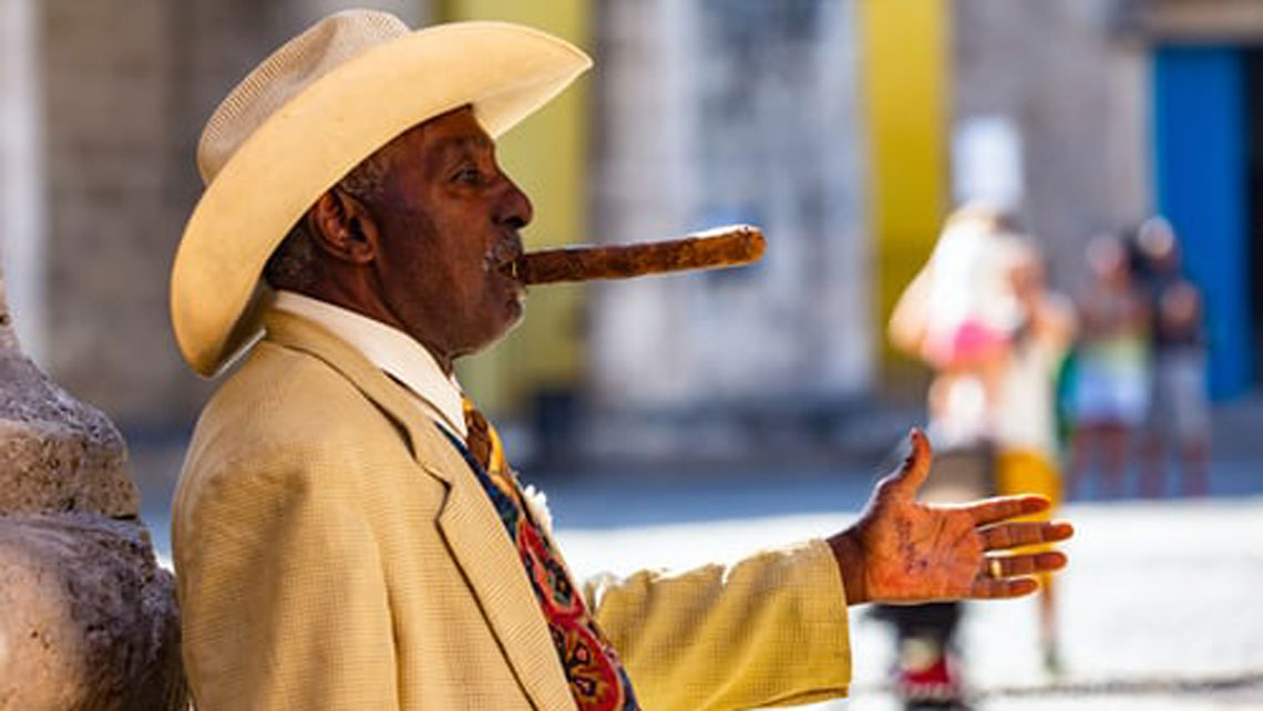 An old man wearing hat and smoking cigar