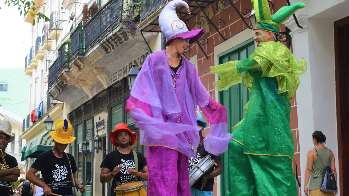 Street dancers on stilts and musicians with drums in Old Havana
