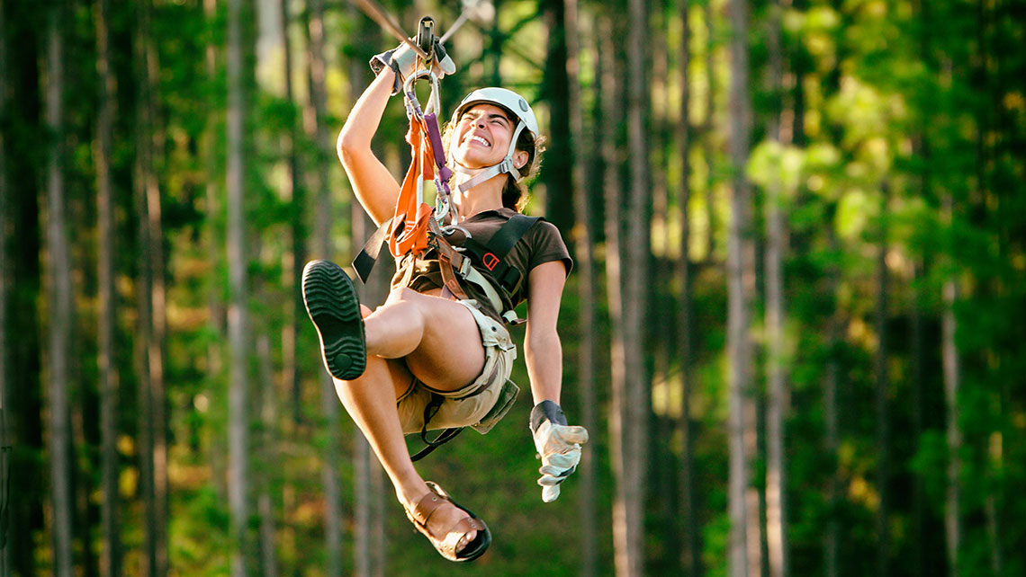 Young woman enjoying canopy-zip-lining in Cuba
