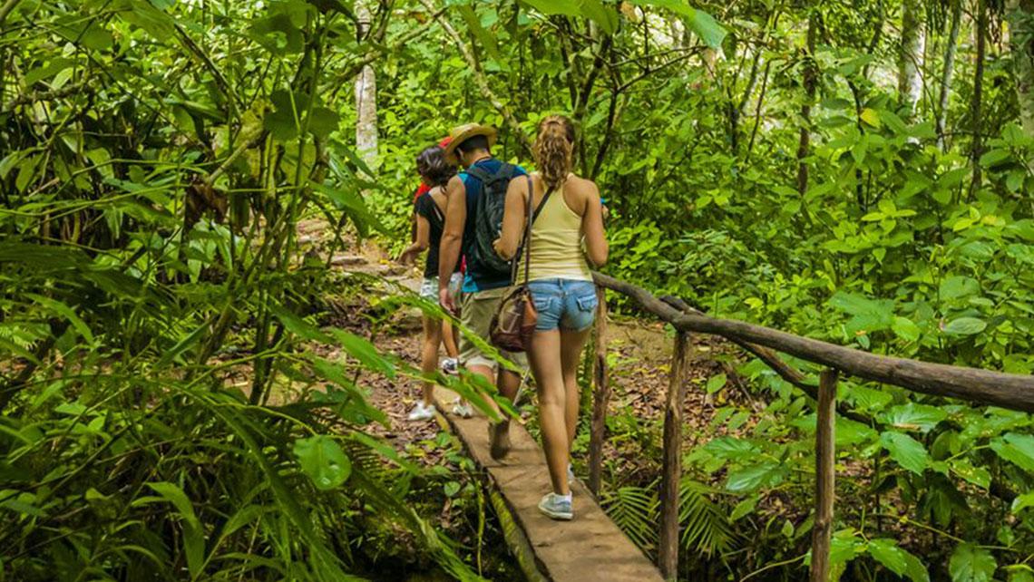 People walking across a rustic bridge on their way to El Nicho waterfalls
