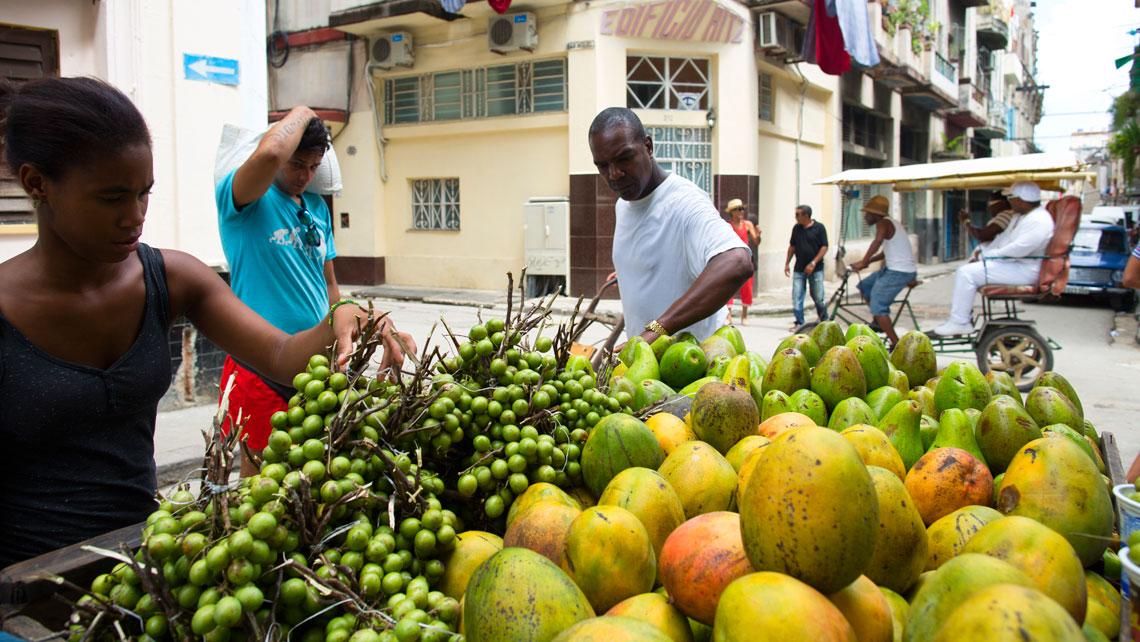 Cuban choosing fruits to buy from a cart