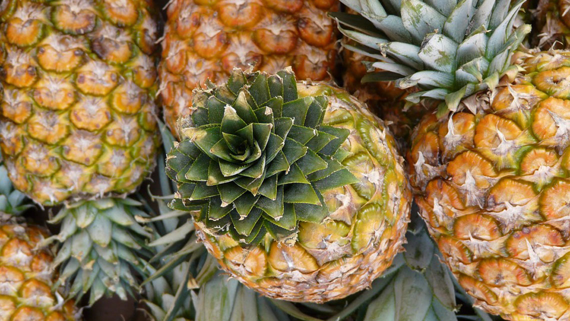 A close up of pineapples in a farmer's market in Havana
