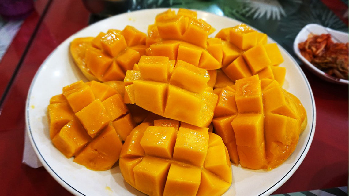 Sliced mango in square pattern in a white plate