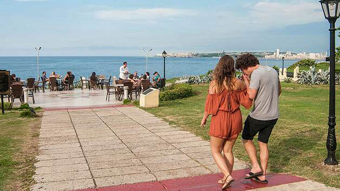 A young couple walking toward an outdoor seating area overlooking the sea in Havana