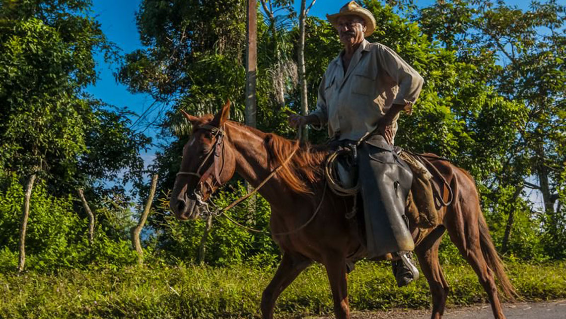 Cuba - Cienfuegos - Escambray Mountains - A guajiro riding a horse