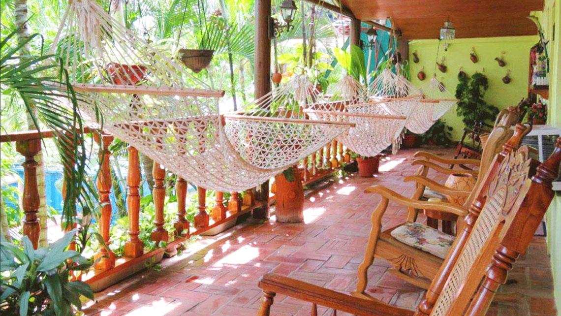 Wooden rocking chairs near hammocks in a veranda of a casa particular