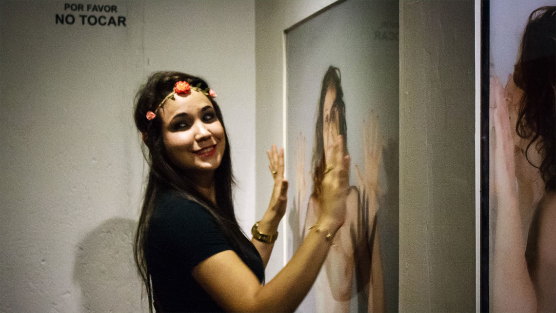 A young woman posing for a photo in front of an artwork in Cuban Art Factory