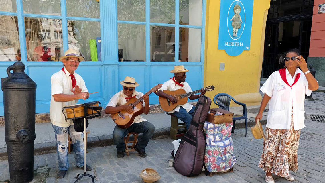 A group of musics wearing traditional clothes playing Cuban music on a street of Havana