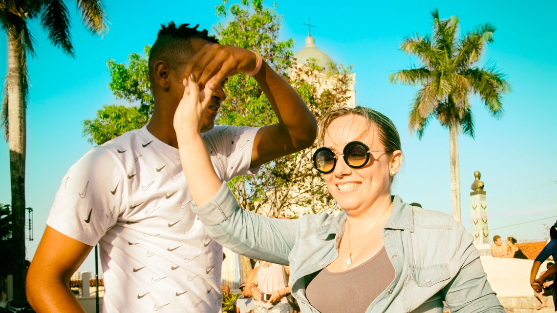 A young woman dancing salsa with a Cuban
