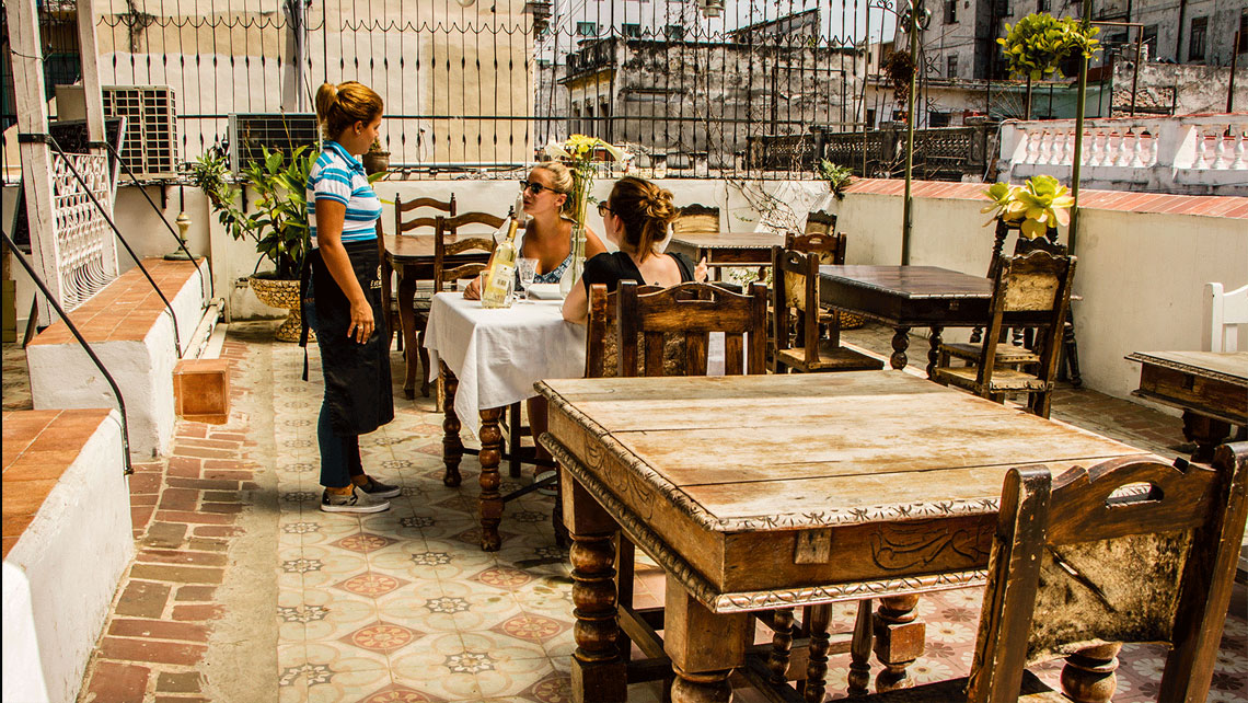 Two young women ordering their lunch in a paladar in Havana