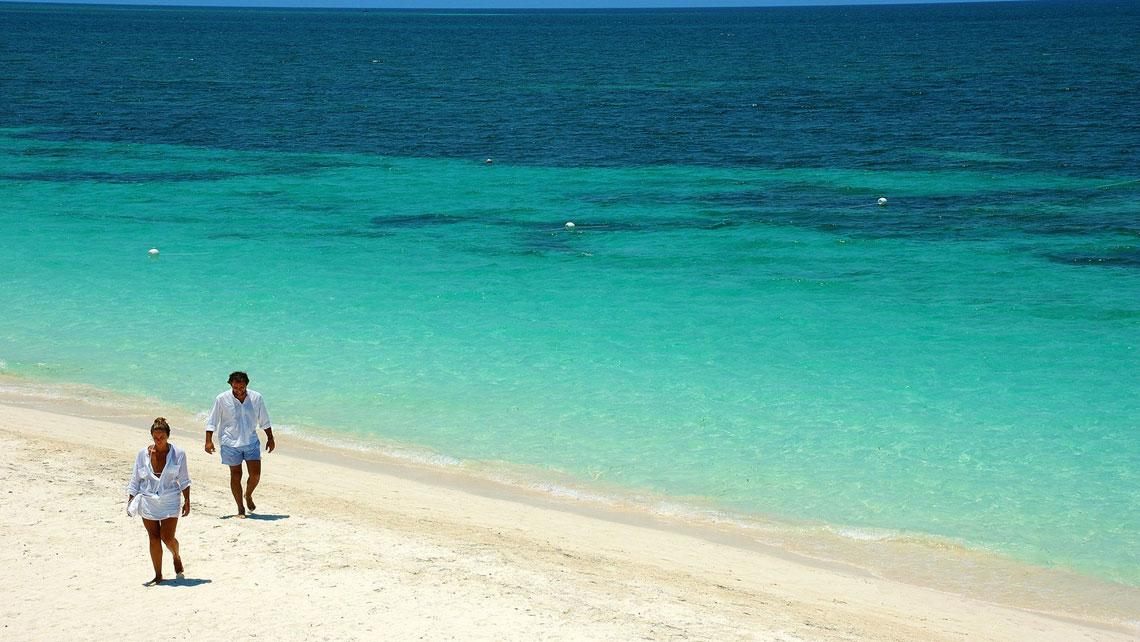 Tourist couple walking on powdery sands