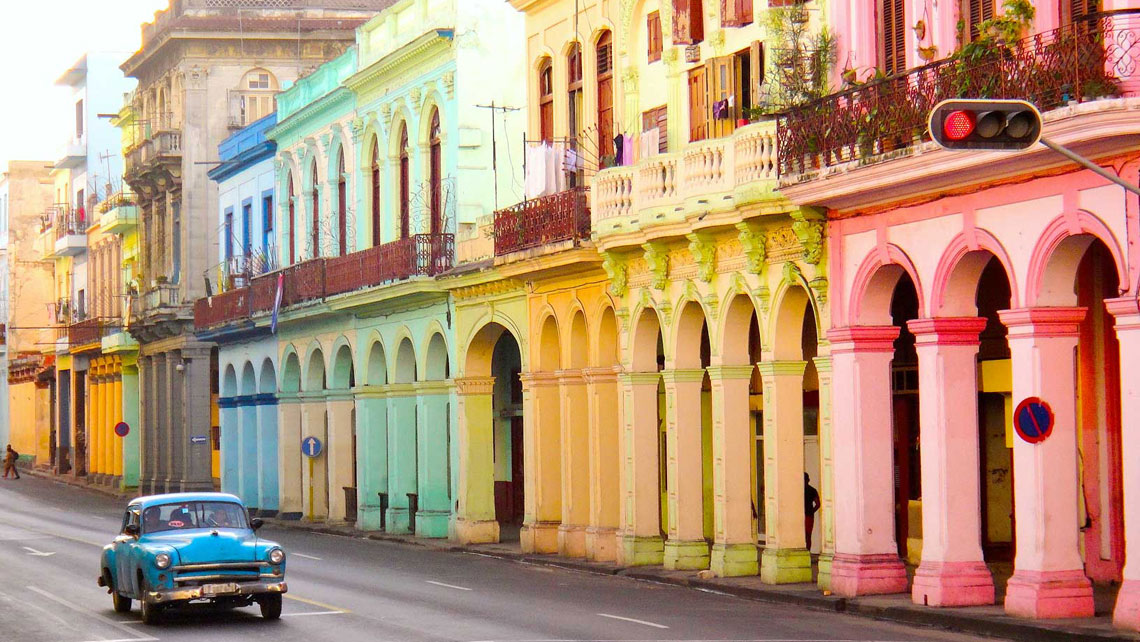 A vintage american car passing by colourful buildings in Havana
