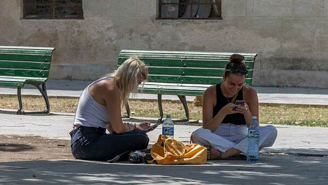 Young women seating on a floor and looking at their mobile phones