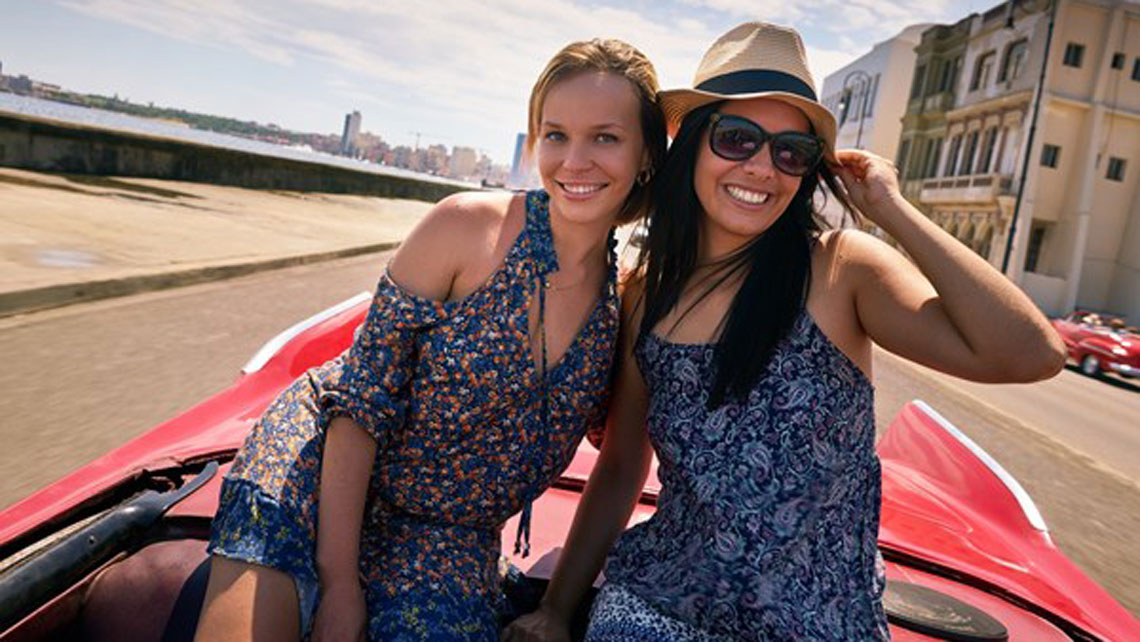 Young women posing to the camera from a vintage american car in Havana