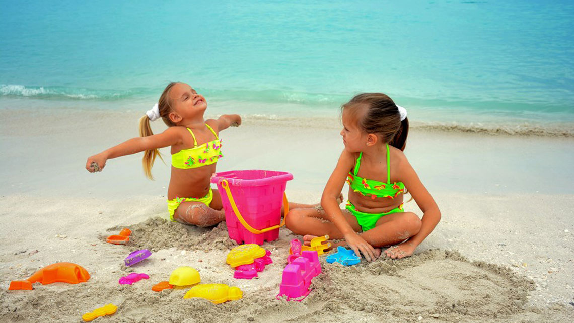 Two young girls playing with sand on the beach