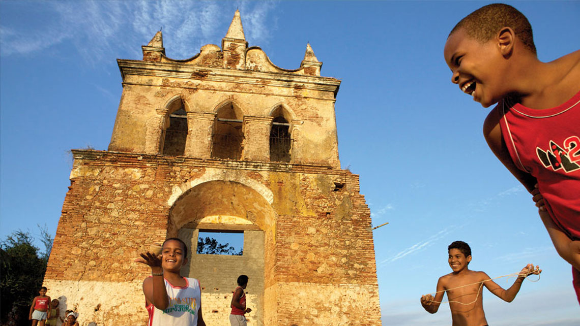 Cuban children playing near an old colonial building