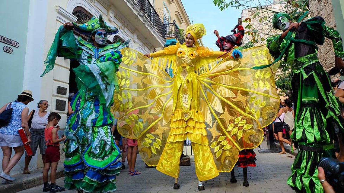People dancing on stilts wearing colourful customes in Old Havana