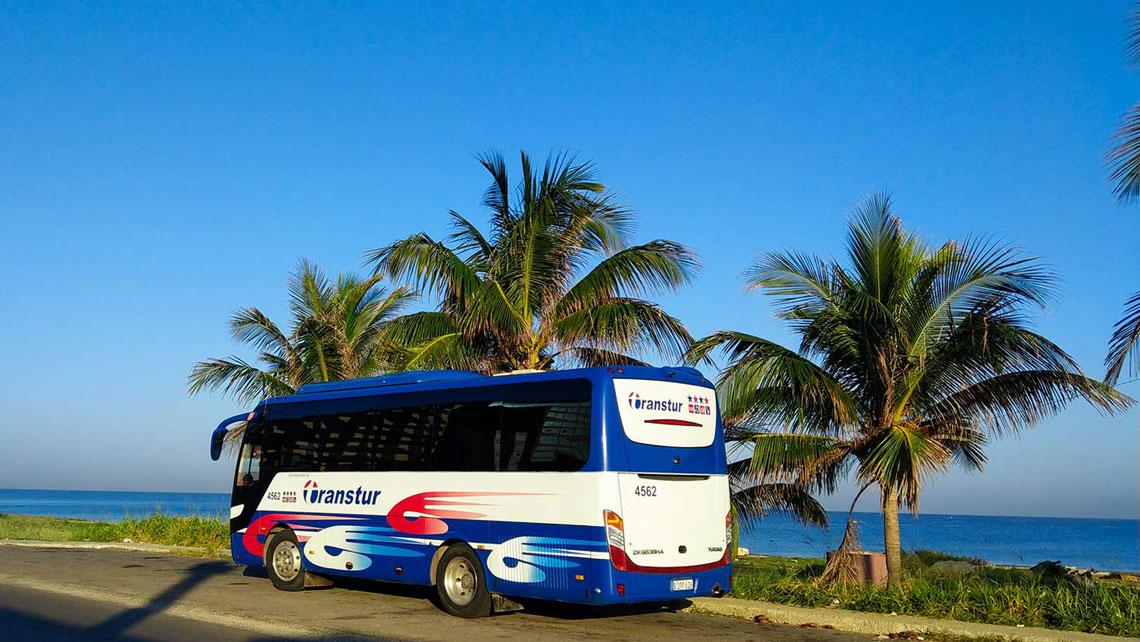 A Transtur coach on a road near the sea
