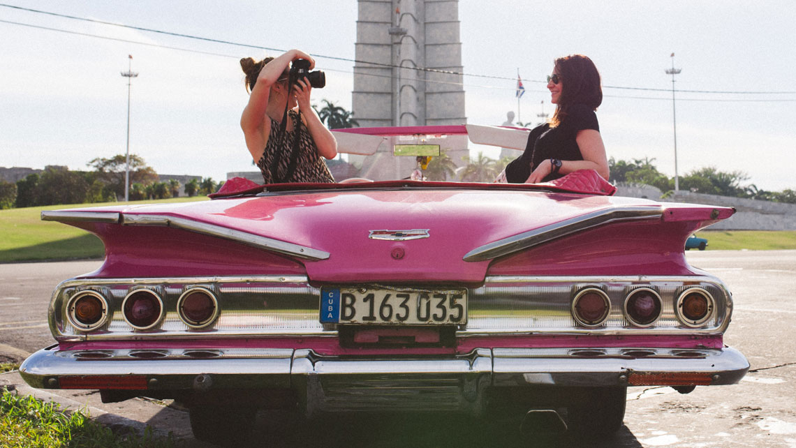 A young woman takes a picture of a fellow traveller on an old vintage car in Havana
