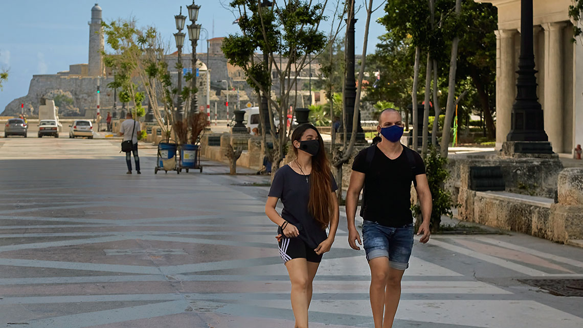 Two young people wearing face masks walking on Paseo del Prado in Havana