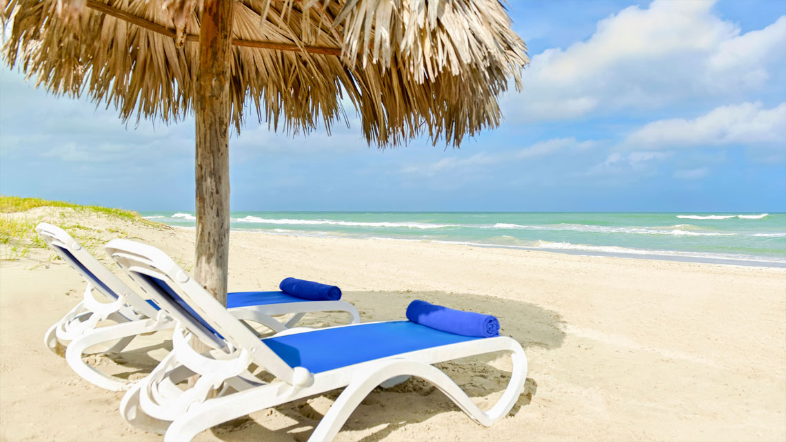 Two empty blue cushioned sun loungers under a rustic parasol on a sandy beach in Cuba