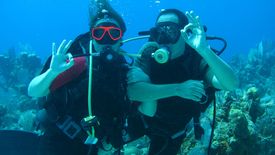 Two scuba divers give ok signal in a Cuba's diving spot