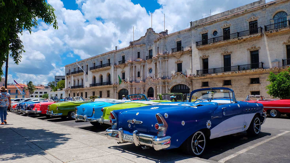 Colourful old vintage cars in a parking lot across Seminario San Carlos in Havana