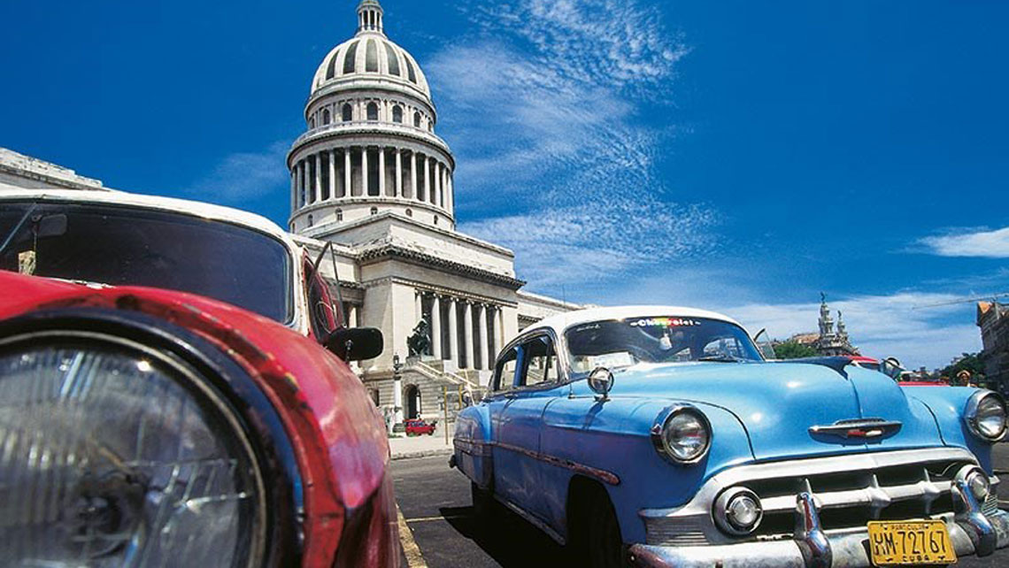 Old vintage American cars parked near El Capitolio in Havana