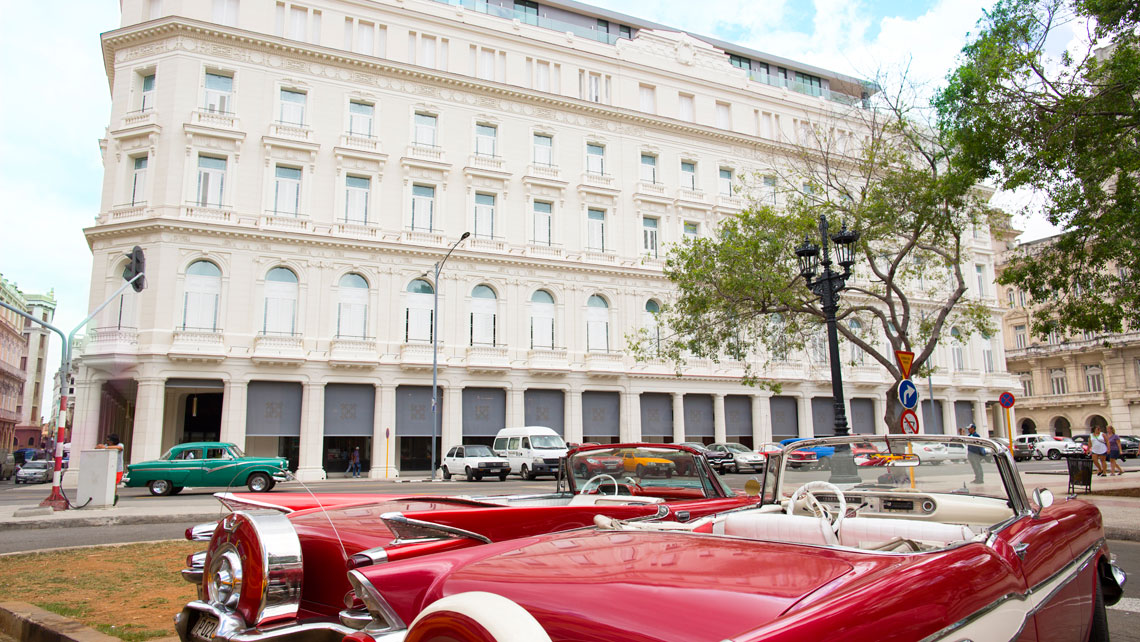Old vintage cars parked across Gran Hotel Manzana Kempinski, La Habana