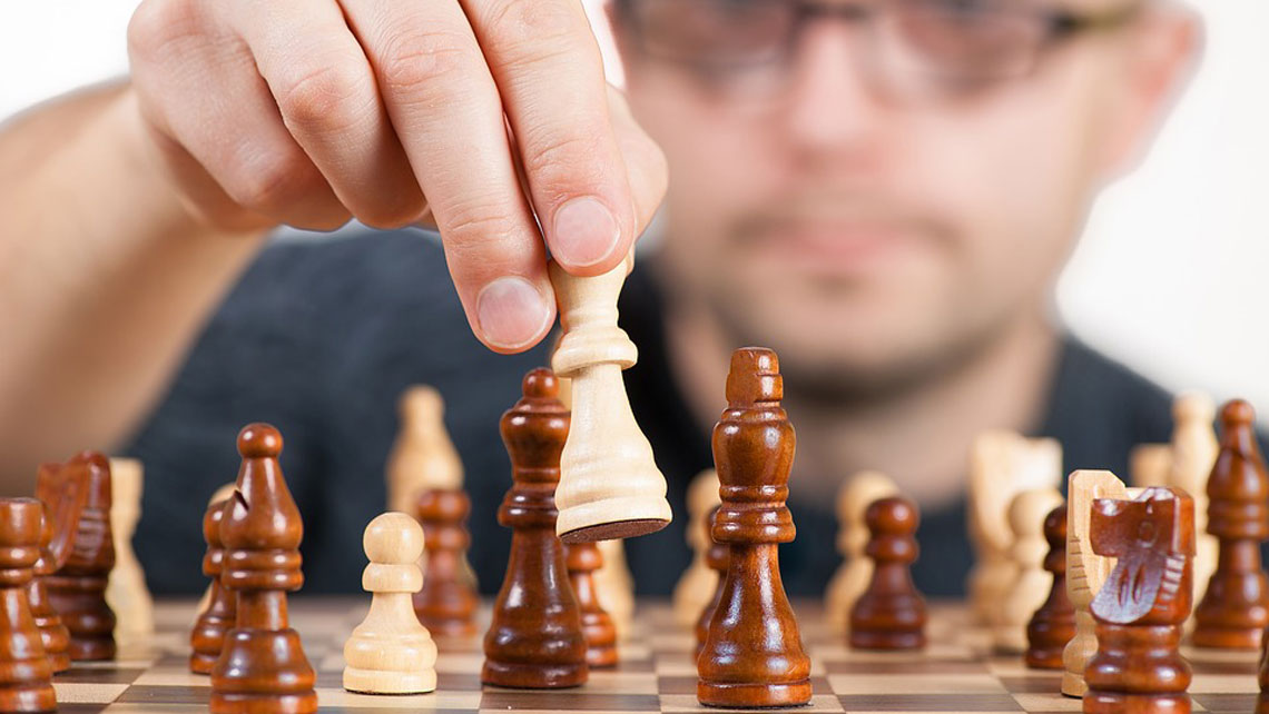 A man's hand takes a white chess knight and prepares to make his move