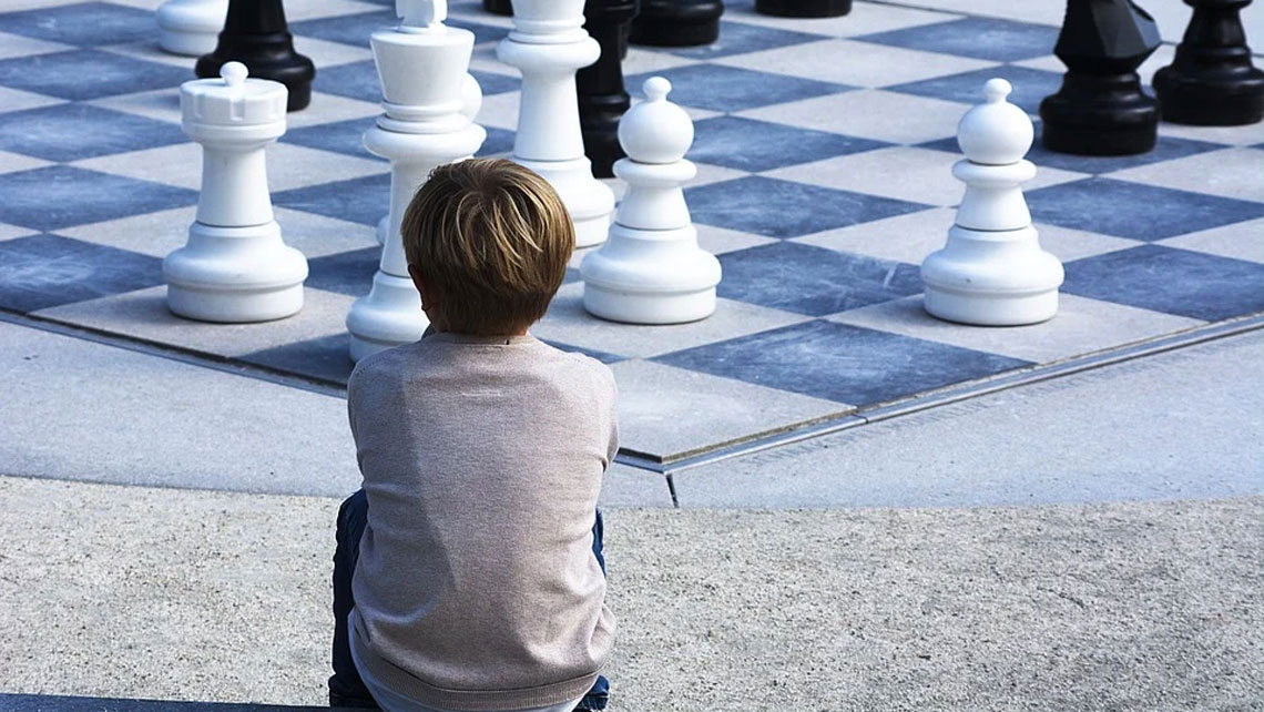 A boy examining a chess game board