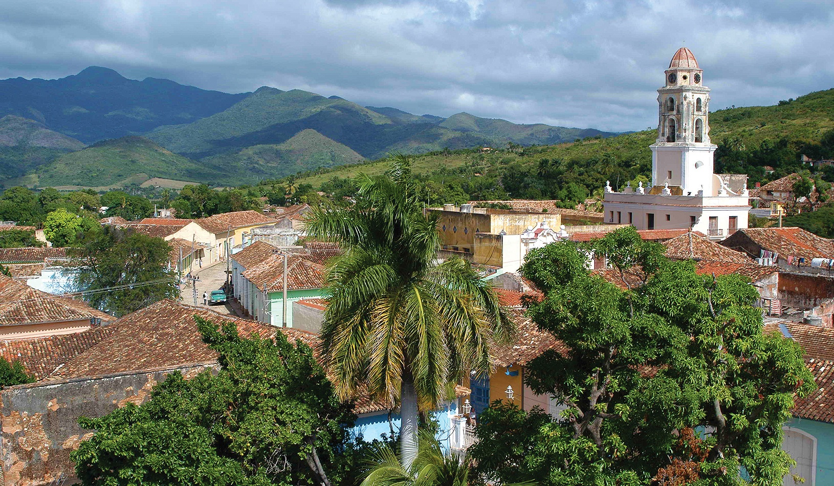 Panoramic view over the city of Trinidad, Cuba with mountains in the background and a cloudy sky
