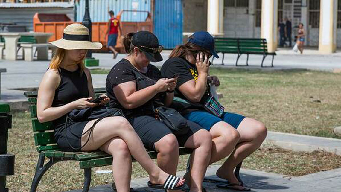 A young tourist wearing a hat using a smartphone in Cuba