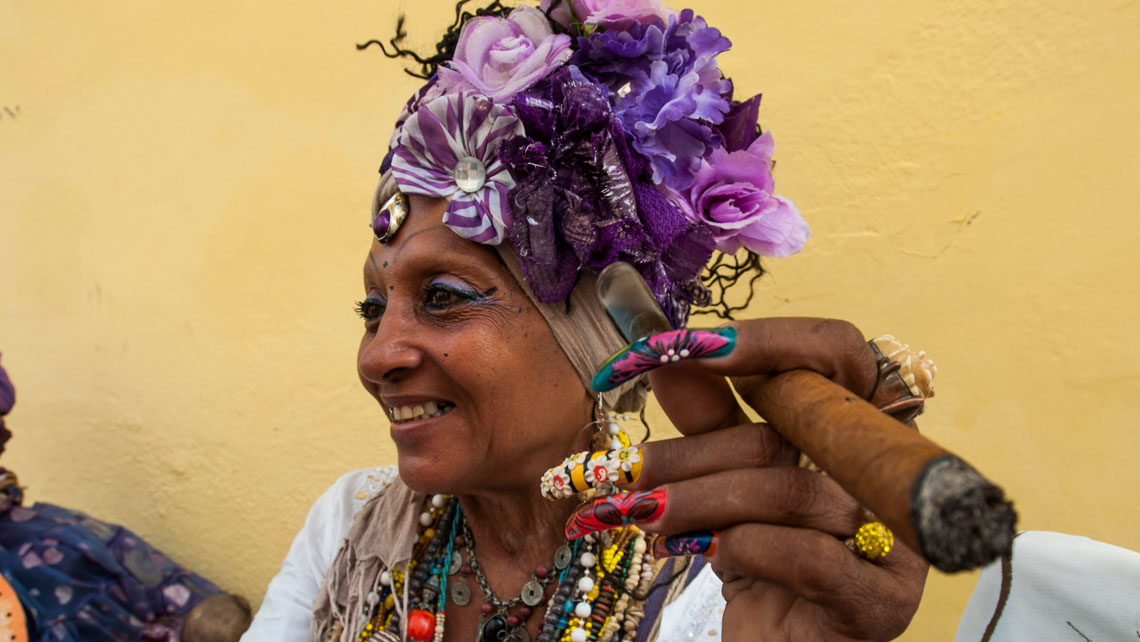 A woman with a cigar and colorful headpiece is seen on the street in Old Havana
