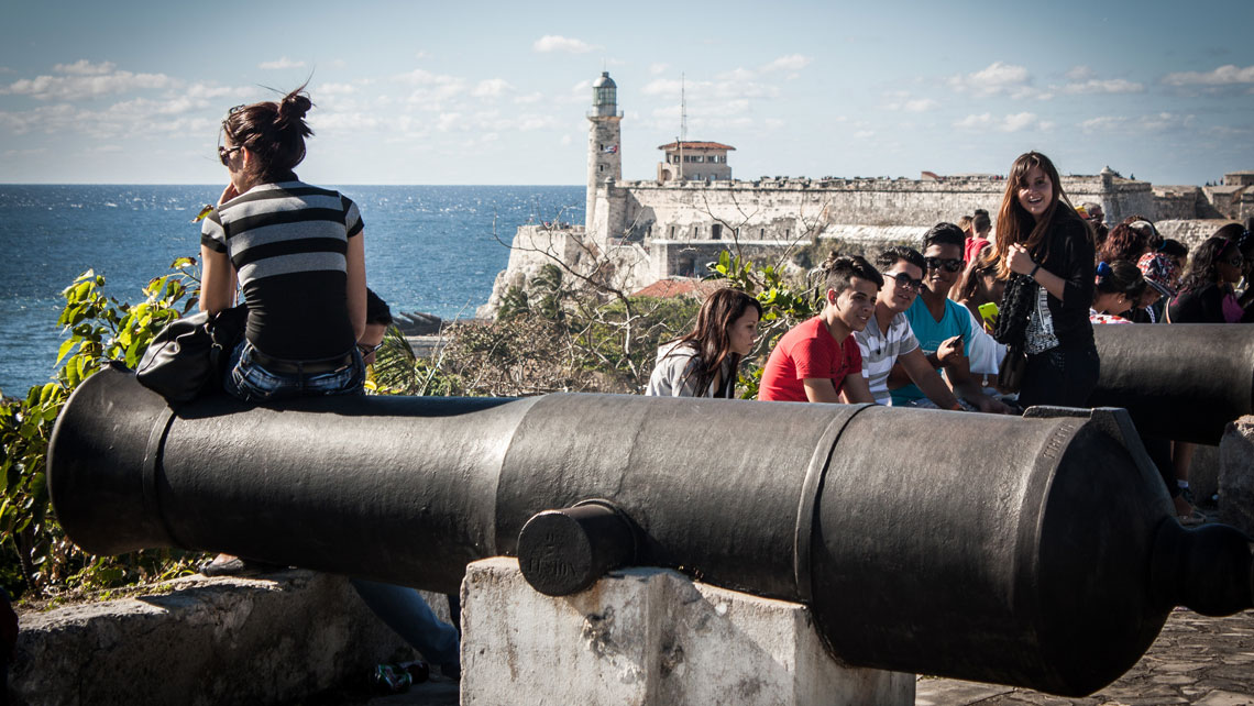 People seating a the walls of La Cabaña just at the entrance of Havana Bay
